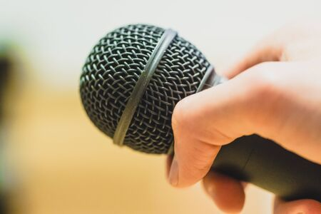 Close up picture of a hand which is holding a black microphone.