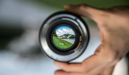 Hand holding camera lens with old city of Salzburg in it, close up Editoriali