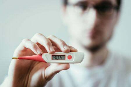 Man holds a red fever thermometer with high temperature in his hand, blurry face