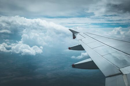 View of a grey airplane wing through the aircraft window. Global warming.