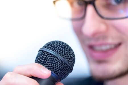 Microphone in the foreground, man taking into it in the blurry background 版權商用圖片