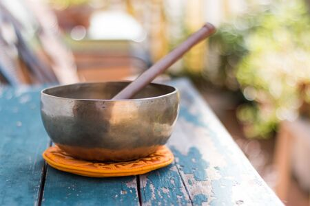 Metal singing bowl on a rustic green, wooden table outdoors. Flowers in the colourful, blurry background Standard-Bild