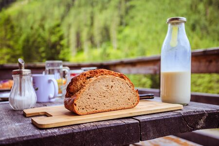 Fresh dark crisp bread for breakfast on an alpine hut. Wooden cutting board and milk in glass bottle.