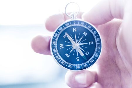 Closeup of a mans hand holding a compass in his hand. Concept for business, innovation Banque d'images