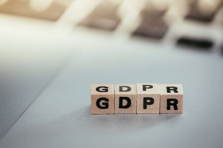 """GDPR: Wooden cubes with letters """"GDPR"""" lying on a laptop. General Data Protection Regulation Zdjęcie Seryjne"""