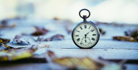 Vintage pocket watch on a wood board, colourful leaves, autumn Stock Photo