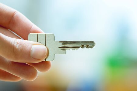 Holding a house key in the hand: New home and property.