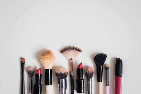 Set of makeup brushes and other accessories. Lipstick, mascara, nail polish, eyeshadow, powder, eyelash and foundation. Products for makeup on white background, top view. Stock Photo