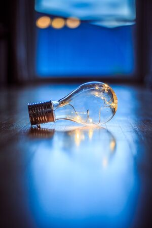 LED light bulb is lying on the wooden floor. Symbol for ideas and innovation. Window and light in the blurry background.