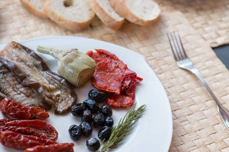 Italian antipasti as dinner appetizer. Tomatoes, Olives, paprika and more.