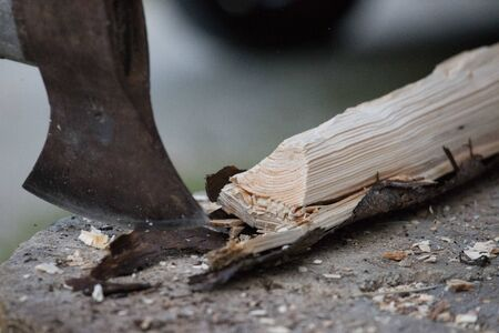 Sharpe axe is cutting wood for making fire, close up picture