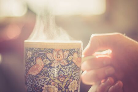 Steaming tea cup and sunlight, warm-up in winter Stock fotó