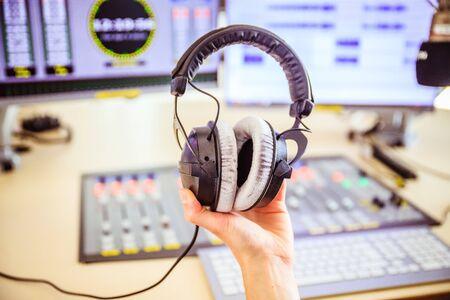 Studio recording: Young is holding headphones in the recording studio, studio in the blurry background
