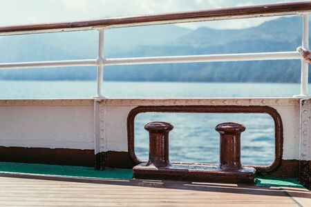 Railing of a boat, boat tour. Blue water and mountain range, Lago di Garda, Italy