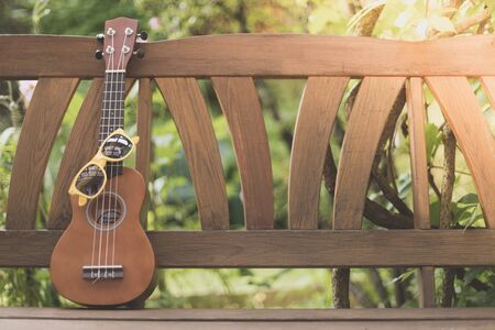 Ukulele and yellow sunglasses on a wooden park bench in summer, green area in the blurry background Stock Photo