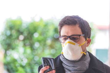 Young business man outdoors with a breathing mask and smartphone. Flue and corona season.