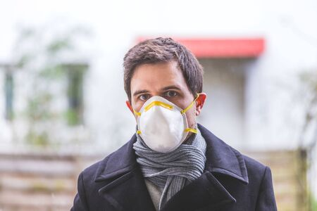 Young man outdoors with a breathing mask. Flue and corona season.