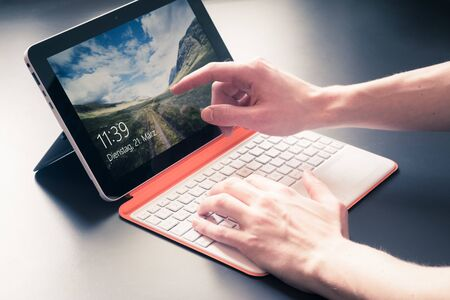Male hands and white orange convertible laptop