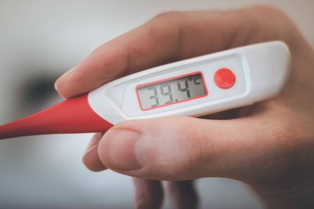 Man holds a red fever thermometer with 39 degrees Celsius in his hand