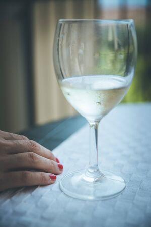 Glass of white wine and hand of a woman on a table