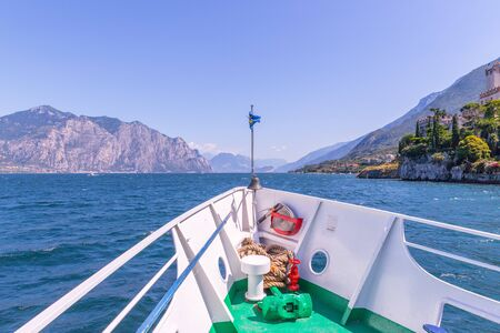 Bow of a boat on a boat tour. Blue water, mountain range and little village, Lago di Garda, Italy