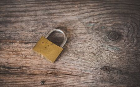 Padlock is lying on rustic wooden desk, close up
