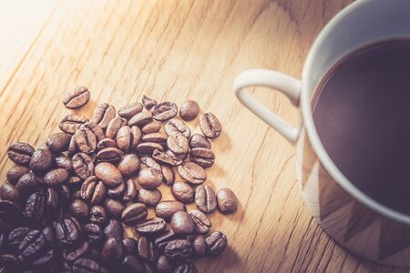 Fresh roasted coffee beans and mug on wooden table, background texture Standard-Bild