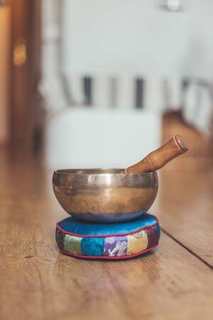 Metal singing bowl on a rustic wooden floor.