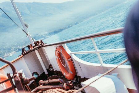 Bow of a boat with safety buoy on a boat tour. Blue water and mountain range, Lago di Garda, Italy Stock fotó