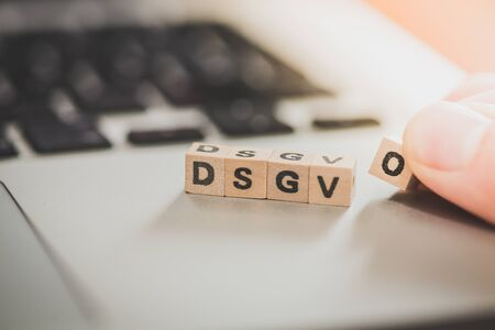 "Wooden cubes with the letters ""DGSVO"" for Datenschutzgrundverordnung are lying on a laptop"