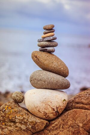Close up picture of a stone cairn outdoors. Ocean in the blurry background Standard-Bild