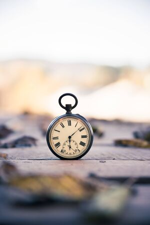 Vintage pocket watch on a wood board, colourful leaves, autumn Banque d'images - 142153908
