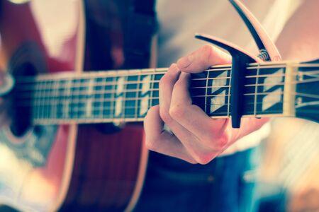 Young man playing a sunburst western guitar: cut out, blurry Banco de Imagens