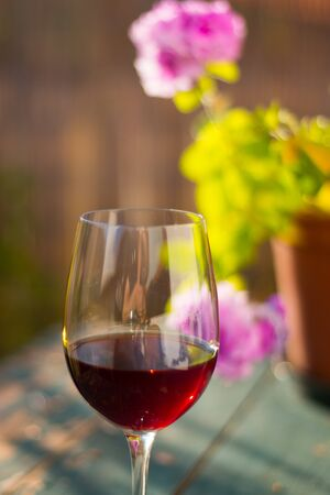 Glass of red wine on an old, rustic wood table. Enjoying it in the own garden in the evening sun. Banque d'images - 142153649