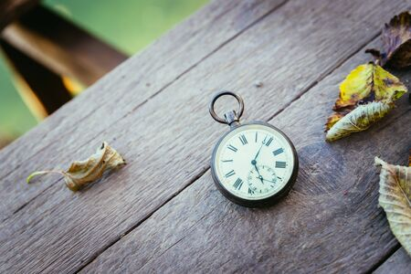Vintage pocket watch on a wood board, colourful leaves, autumn Banque d'images - 142154388
