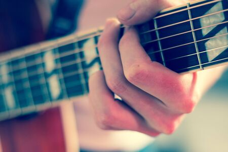Young man playing a sunburst western guitar: cut out, blurry Imagens