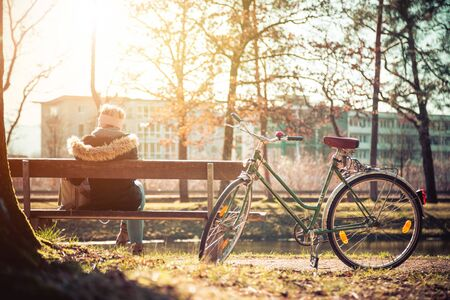 Back view of young woman with bicycle who is enjoying the sun on a park bench, spring time