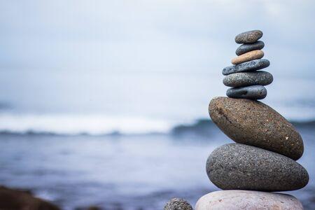 屋外の石のケアンの写真をクローズアップ。ぼやけた背景の海 写真素材
