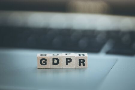 "GDPR: Wooden cubes with letters ""GDPR"" lying on a laptop. General Data Protection Regulation"