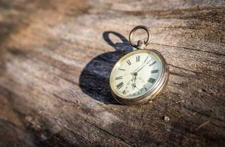 Vintage watch lies on a wood board, autumn time