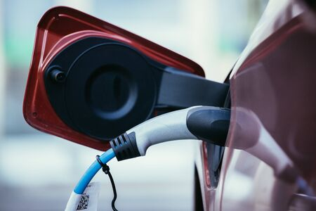 Electric car recharging with charge cable and plug leading to charge point Stockfoto