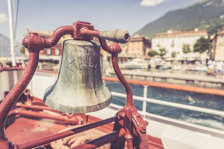Bow of a boat with boat bell on a cruise tour. Blue water, mountain range and cute little village at Lago di Garda, Italy