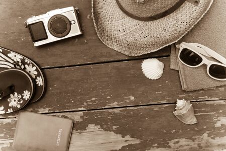 Summer background: Concept of leisure travel in the summer: Straw hat, sunglasses, flip flops, shells, vintage camera, towel and passport.  版權商用圖片
