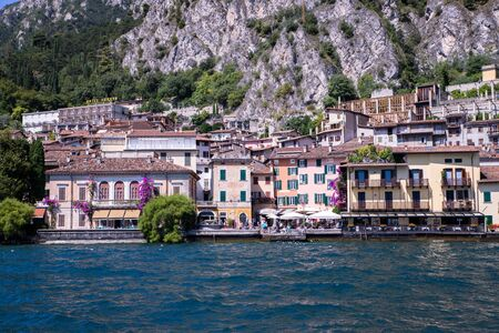 Idyllic coastline scenery in Italy, captured from the water. Blue water and a cute village at lago di garda, Limone