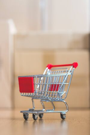 Online-Shopping and parcel service concept: Miniature shopping cart and cardboard boxes