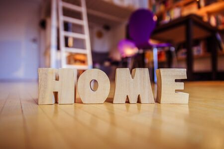 Wooden HOME Letters on the floor of an apartment