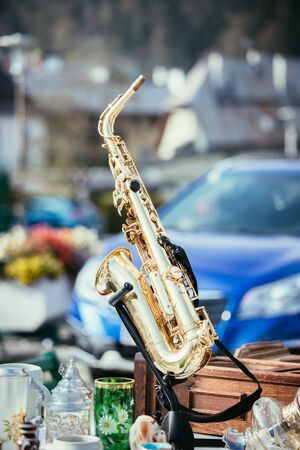 Golden saxophone on a flea market, outdoors