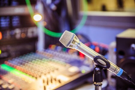 Metal microphone in the studio, cables and buttons in the blurry background