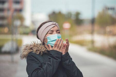 Young sneezing woman outdoors wearing a face mask. Corona and flu season.