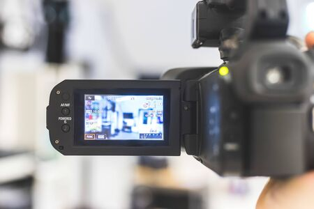 Male cameraman is holding a professional video camcorder, blurry background